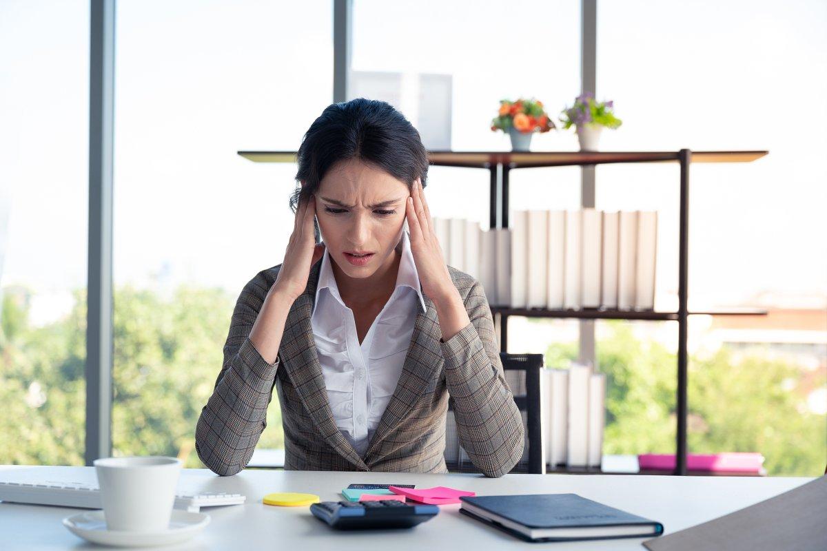 zestresowana kobieta siedzi przy biurku i dłonie trzyma na skroniach