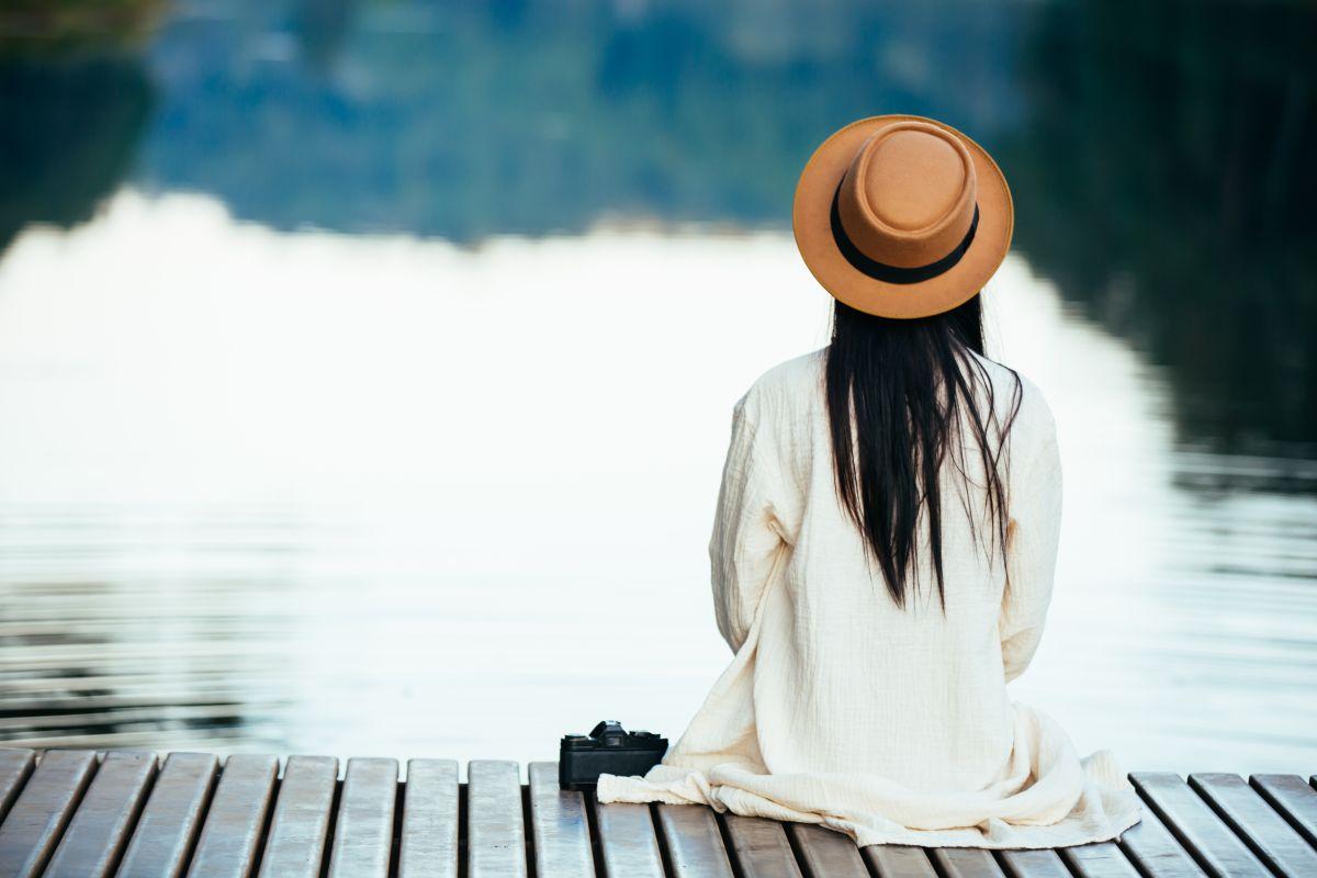 kobieta siedzi sama na pomoście nad jeziorem