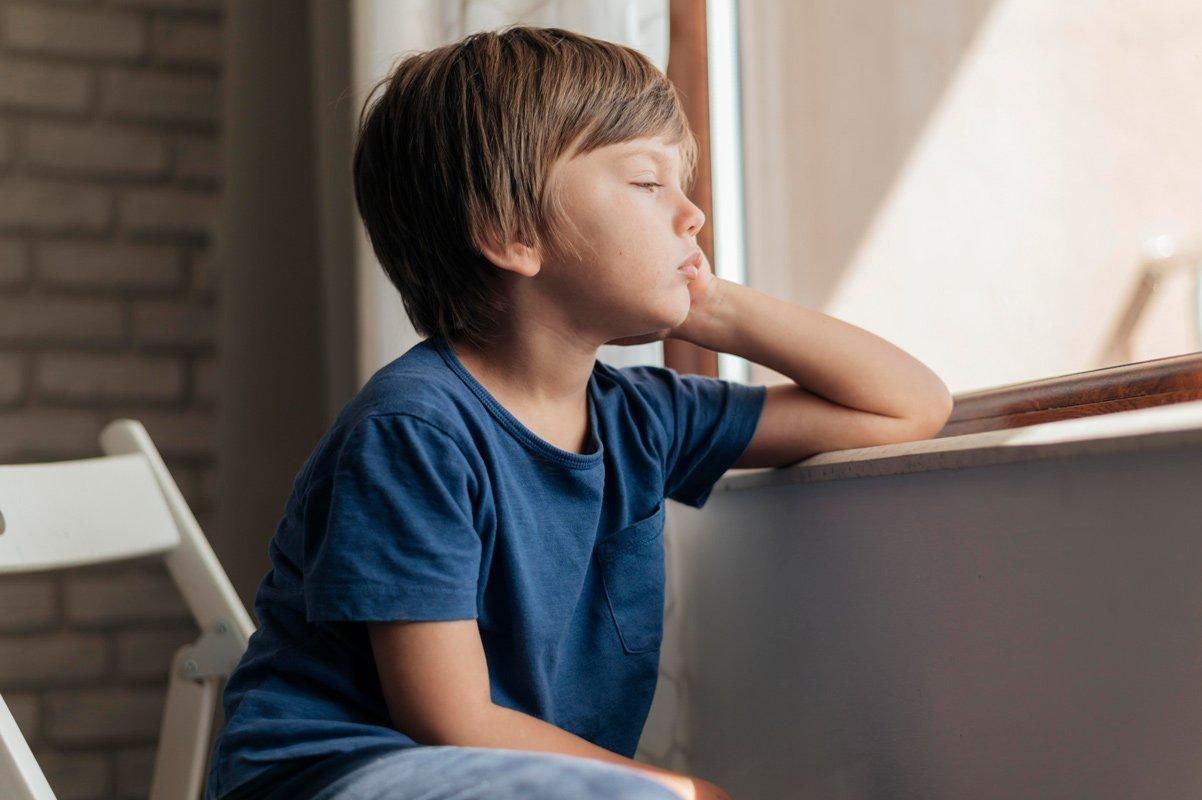 smutny chłopiec patrzy przez okno