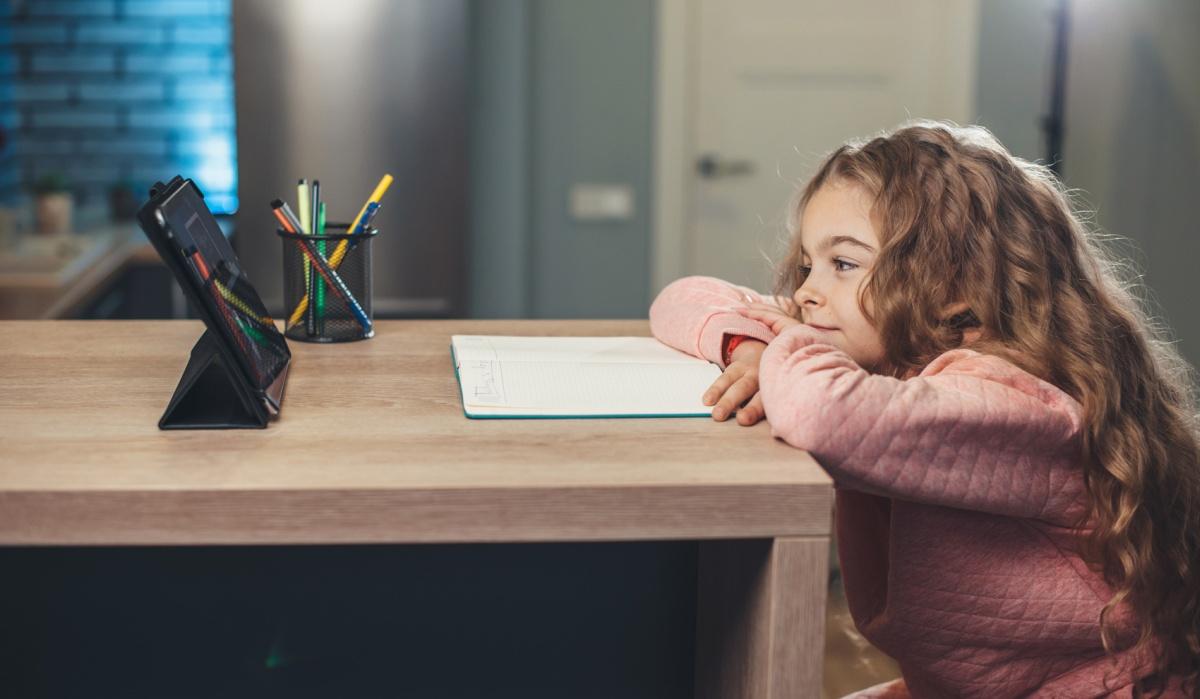 dziewczynka siedzi przy stole przy laptopie