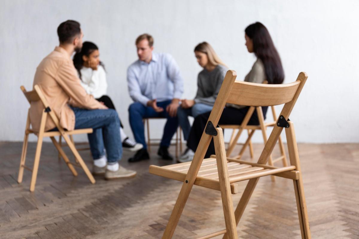 grupka ludzi rozmawia siedząc na krzesłach