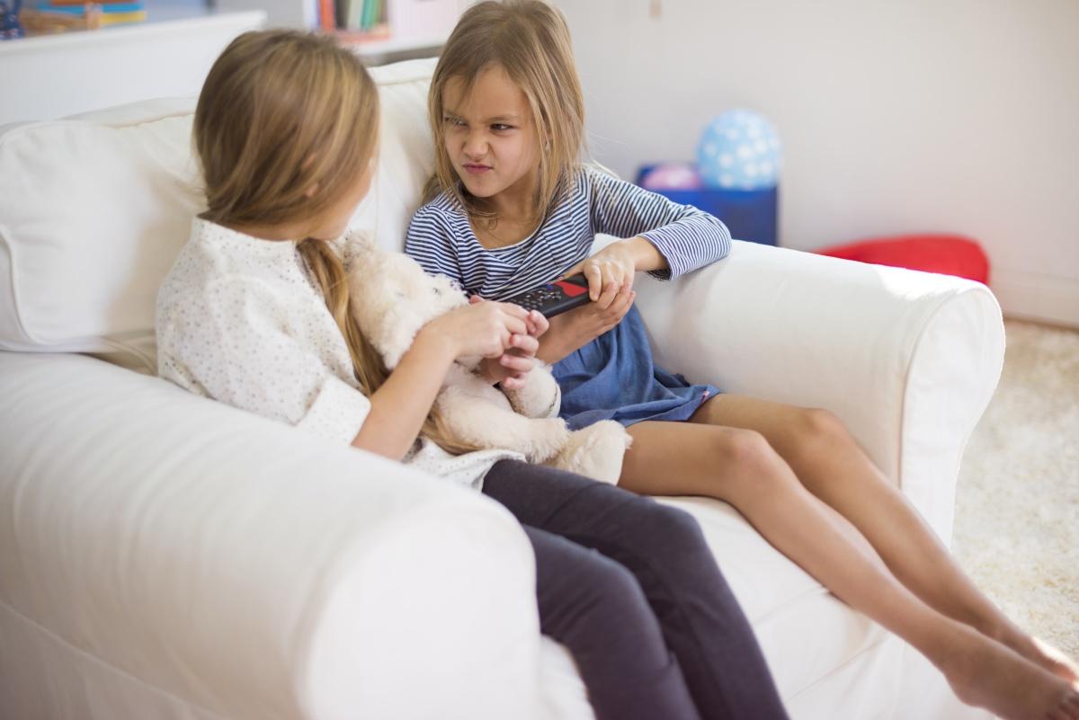 dwie dziewczynki kłócą się o pilota od telewizora